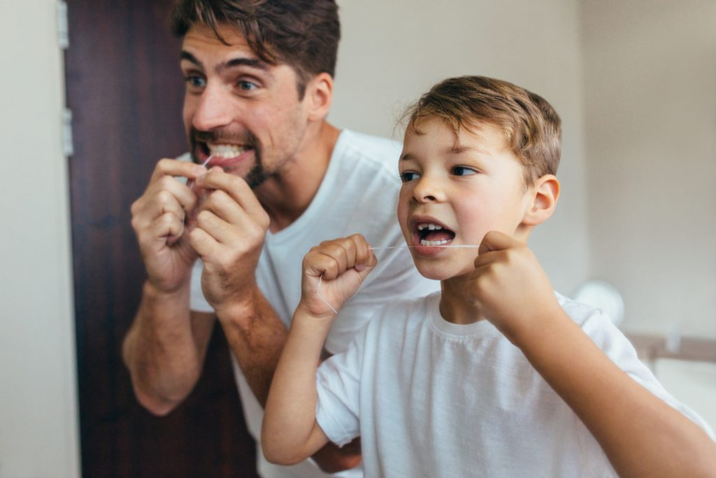 Father and son practicing preventative dentistry