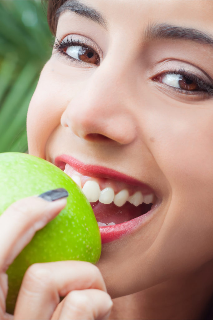 Woman biting into an apple to show strength of dental implants
